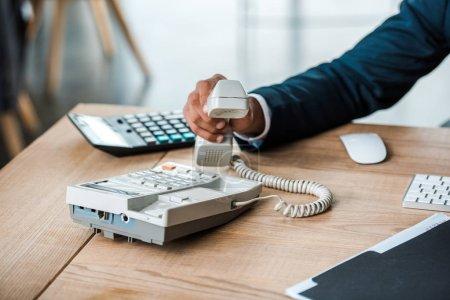 Photo pour Vue recadrée de l'homme d'affaires retenant le téléphone rétro dans le bureau - image libre de droit