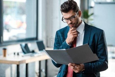 Photo for Pensive businessman in glasses looking at folder and touching face - Royalty Free Image