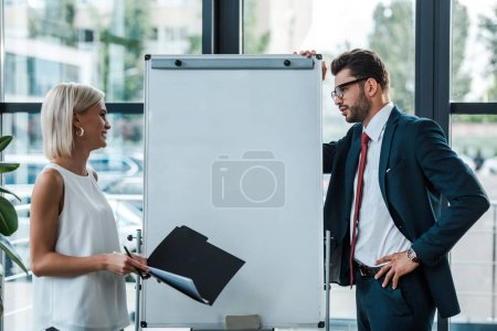 Photo for Handsome businessman in glasses standing with hand on hip and looking at woman with folder and pen - Royalty Free Image