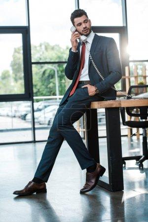 Photo pour Homme d'affaires beau avec la main dans la poche parlant sur le téléphone rétro dans le bureau moderne - image libre de droit