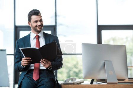 happy bearded man holding notebook near computer monitor in office