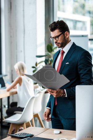selective focus of handsome businessman in glasses looking at folder near coworker