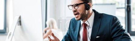 Foto de Foto panorámica del hombre emocional en gafas y auriculares que trabajan en la oficina - Imagen libre de derechos