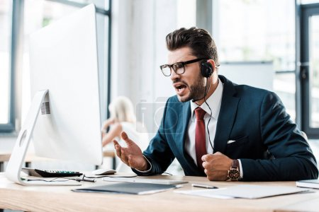 Foto de Enfoque selectivo del hombre emocional en gafas y auriculares que trabajan en la oficina - Imagen libre de derechos