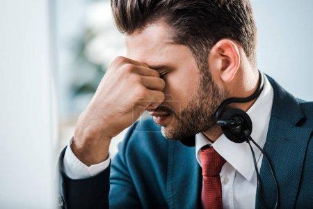 homme d'affaires fatigué dans un casque avec les yeux fermés couvrant le visage dans le bureau
