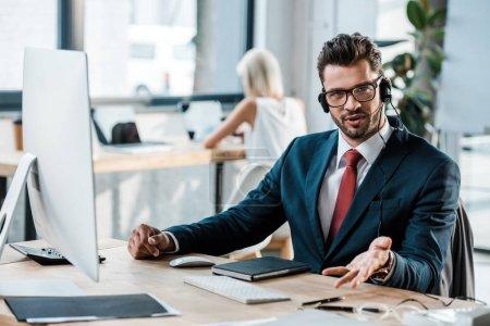 Photo pour Foyer sélectif de barbu homme d'affaires dans les lunettes et les gestes casque dans le bureau - image libre de droit