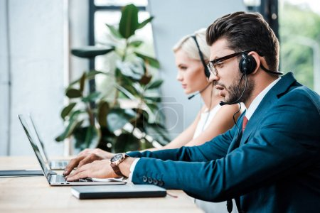 Photo pour Foyer sélectif de bel homme dans la dactylographie casque sur ordinateur portable tout en travaillant près de collègue - image libre de droit