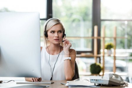 selective focus of beautiful operator touching headset while working in office