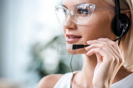 Foto de Primer plano de atractivo operador rubio en gafas tocando auriculares - Imagen libre de derechos