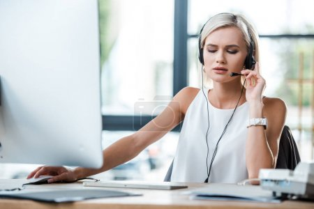 selective focus of beautiful blonde woman touching headset and working in office
