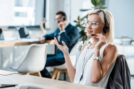 selective focus of happy operator touching headset, talking and gesturing near coworker
