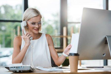 Photo pour Foyer sélectif de femme d'affaires blonde attirante souriant tout en parlant sur le téléphone rétro près de tasse de papier - image libre de droit