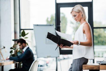 Photo pour Foyer sélectif de femme d'affaires blonde dans le dossier de fixation de glaces et les documents près du collègue dans le bureau moderne - image libre de droit