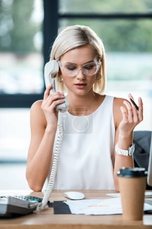 Photo for Selective focus of businesswoman in glasses looking at documents and talking on retro phone near paper cup - Royalty Free Image