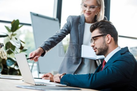 Photo for Selective focus of man near blonde coworker holding pen near laptop - Royalty Free Image