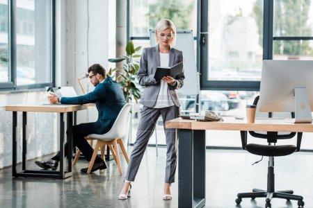 Photo pour Attrayant homme d'affaires dans des lunettes regardant ordinateur portable tout en restant au bureau près de collègue - image libre de droit