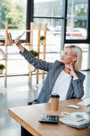 Foto de Enfoque selectivo de la mujer de negocios en gafas tomando selfie en la oficina moderna - Imagen libre de derechos