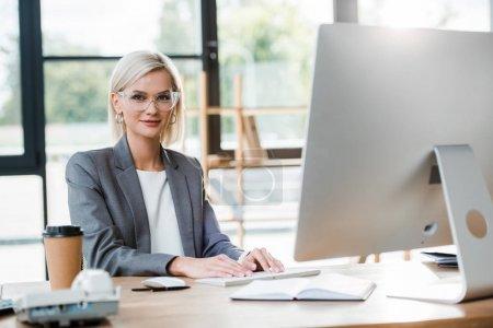 Photo pour Foyer sélectif de femme d'affaires heureuse dans des glaces travaillant dans le bureau moderne près de tasse de papier - image libre de droit