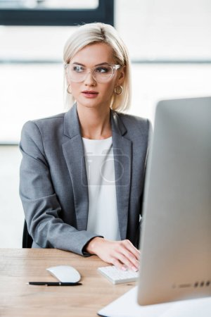 Photo for Selective focus of beautiful businesswoman in glasses working in modern office - Royalty Free Image