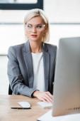 """Постер, картина, фотообои """"селективное внимание красивой бизнес-леди в очках, работающих в современном офисе"""""""