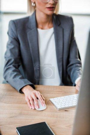 Photo pour Vue recadrée de femme d'affaires utilisant la souris d'ordinateur dans le bureau - image libre de droit