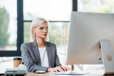 Photo pour Focus sélectif de femme d'affaires attrayante tapant sur le clavier d'ordinateur dans le bureau - image libre de droit