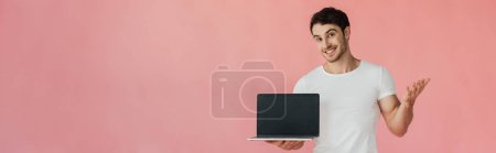 panoramic shot of smiling young man in white t-shirt showing laptop with blank screen isolated on pink