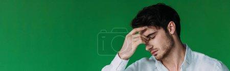plano panorámico de hombre joven cansado con los ojos cerrados tocando la frente aislado en verde