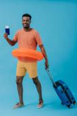 "Постер, картина, фотообои ""positive african american tourist standing with passport and luggage on blue """