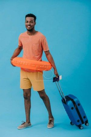 Photo pour Touriste américain africain gai restant avec le passeport et les bagages sur le bleu - image libre de droit