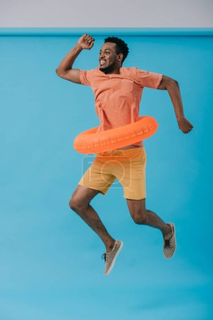 Photo for Happy bearded african american man jumping with swim ring on blue - Royalty Free Image