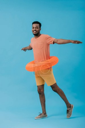 happy bearded african american man with swim ring and outstretched hands on blue