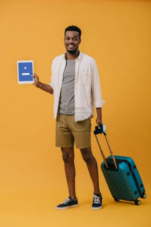Photo for KYIV, UKRAINE - JUNE 27, 2019: cheerful african american man standing with luggage and holding digital tablet with facebook app on screen on orange - Royalty Free Image