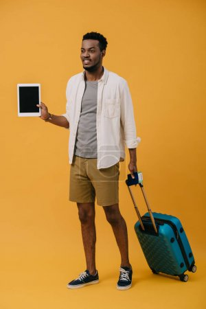 Photo for Happy african american man standing with luggage and holding digital tablet with blank screen on orange - Royalty Free Image