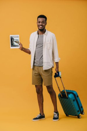 cheerful african american man standing with luggage and holding digital tablet with tickets app on screen on orange