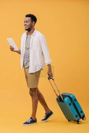 Photo pour Heureux homme afro-américain tenant tablette numérique et marcher avec des bagages sur orange - image libre de droit