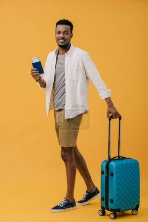 Photo for Cheerful african american man holding passport with air ticket and standing near luggage on orange - Royalty Free Image