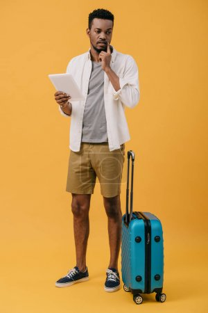 Photo for Pensive african american man holding digital tablet and standing near luggage on orange - Royalty Free Image
