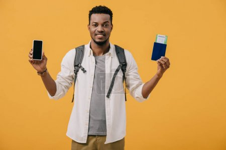 Photo for Happy african american man with backpack holding passport with air ticket and smartphone with blank screen isolated on orange - Royalty Free Image