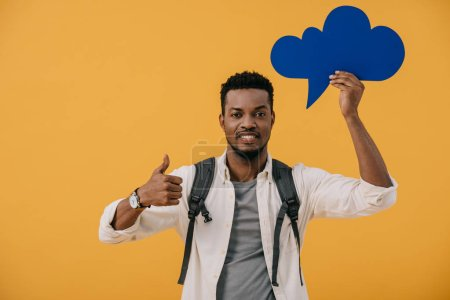 cheerful african american man holding blue thought bubble and showing thumb up isolated on orange