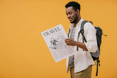 Photo for Cheerful african american man standing with backpack and reading travel newspaper isolated on orange - Royalty Free Image