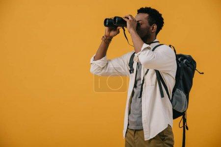 Photo pour Homme américain africain regardant par des jumelles isolées sur l'orange - image libre de droit