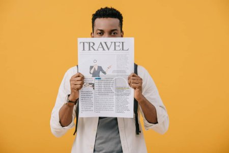 Photo for Curly african american man covering face with travel newspaper isolated on orange - Royalty Free Image
