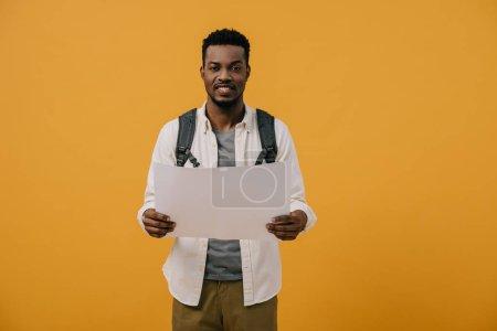 glücklicher afrikanisch-amerikanischer Mann hält leeres Papier isoliert auf orange