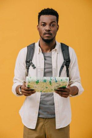 Photo pour Bel homme américain africain avec la carte de fixation de sac à dos d'isolement sur l'orange - image libre de droit