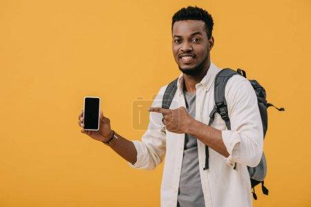 Photo pour Homme afro-américain joyeux pointant du doigt le smartphone avec écran vide isolé sur orange - image libre de droit