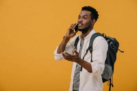 Foto de Hombre afroamericano rizado hablando en el teléfono inteligente mientras está de pie aislado en naranja - Imagen libre de derechos