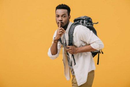 Photo pour Homme afro-américain montrant signe de silence tout en se tenant debout avec sac à dos isolé sur orange - image libre de droit