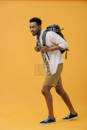 Photo for Curly happy african american man walking with backpack on orange - Royalty Free Image