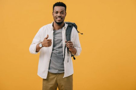 Photo for Happy african american man showing thumb up and touching backpack isolated on orange - Royalty Free Image
